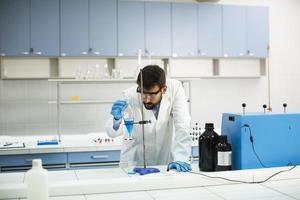 jonge onderzoeker die met blauwe vloeistof bij scheitrechter in het laboratorium werkt foto