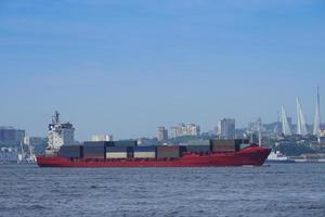 zeegezicht met een rood containerschip en de skyline van de stad op de achtergrond in Vladivostok, Rusland foto