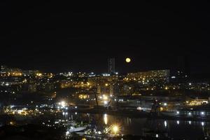 nachtcityscape met een watermassa en gele maan in Vladivostok, Rusland foto