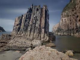 rotsen met rechte randen bij eb van een strand aan de Asturische kust foto
