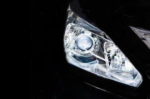 auto koplamp geïsoleerd op zwart foto