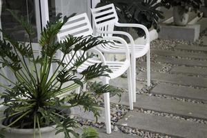 twee witte stoelen in een tuin