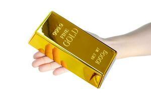 een hand met een goudstaaf van 1 kg op een witte achtergrond