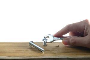 een hand met behulp van een moersleutel die een schroef vastschroeft in een houten plank op een witte achtergrond