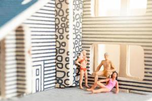 miniatuurmensen die thuis blijven en zichzelf in quarantaine plaatsen om coronavirus te voorkomen, blijf thuis-concept foto