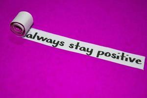 blijf altijd positief tekst, inspiratie, motivatie en bedrijfsconcept op paars gescheurd papier
