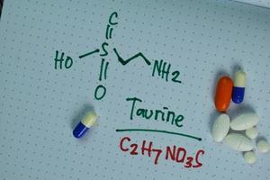 structurele chemische formule geschreven op een boek met pillen die chemicaliën vertegenwoordigen foto