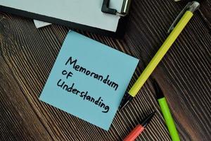 mou - memorandum van overeenstemming geschreven op papierwerk geïsoleerd op een houten tafel foto