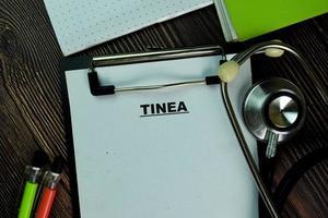 tinea geschreven op papierwerk geïsoleerd op houten tafel
