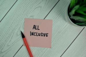 all inclusive geschreven op notitie geïsoleerd op houten tafel
