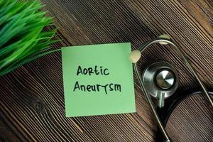 aorta-aneurysma geschreven op notitie geïsoleerd op houten tafel foto
