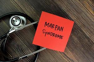 Marfan syndroom geschreven op notitie geïsoleerd op houten tafel foto