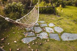 bamboe rieten hangmat aan een boom om te ontspannen in de openbare tuin foto