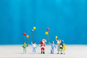 miniatuur kerstman en kinderen met ballonnen, prettige kerstdagen en gelukkig nieuwjaar concept
