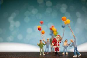 miniatuur kerstman en kinderen met ballonnen, prettige kerstdagen en gelukkig nieuwjaar concept foto