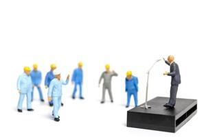 miniatuurmensen die luisteren naar een politicus die spreekt tijdens een verkiezingsbijeenkomst