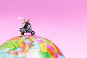 miniatuurpaar rijden op een motorfiets op een wereldbol