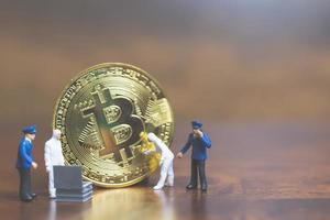 miniatuurpolitie en detectives die zich voor bitcoin cryptocurrency, cybercrime-concept bevinden foto