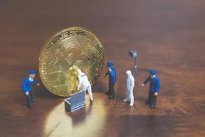 miniatuurpolitie en detectives die zich voor bitcoin cryptocurrency, cybercrime-concept bevinden