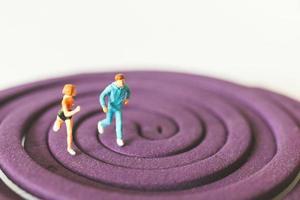 miniatuurpaar dat op een paars cirkelvormig veld loopt foto