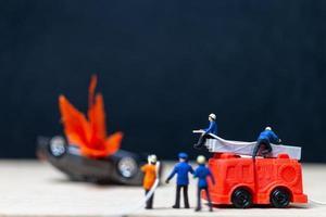 miniatuurbrandweerlieden bij een auto-ongeluk, auto-ongelukconcept