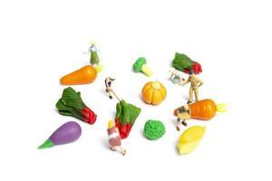 miniatuur tuinders die groenten oogsten op een witte achtergrond, landbouwconcept