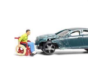 miniatuur man in een rolstoel bij een autowrak op een witte achtergrond