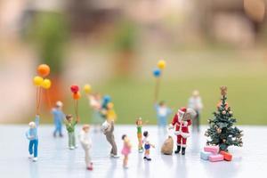miniatuur kerstman met geschenken voor een gelukkig gezin, kerstmis en een gelukkig nieuwjaar concept