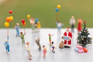 miniatuur kerstman met geschenken voor een gelukkig gezin, kerstmis en een gelukkig nieuwjaar concept foto