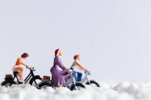 miniatuurreizigers fietsen in de sneeuw, winter achtergrond concept
