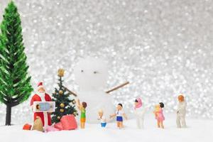 miniatuur kerstman en kinderen met een sneeuw achtergrond, kerstmis en een gelukkig nieuwjaar concept