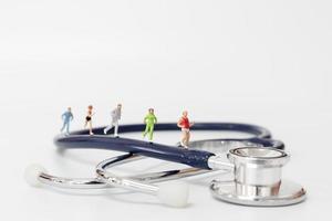 miniatuurmensen die op een stethoscoop, sport en gezond concept lopen