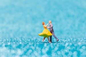 miniatuurpaar dansen op blauwe glitter achtergrond, Valentijnsdag concept