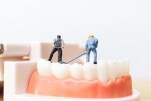miniatuurarbeiders die een tand, gezondheidszorg en medisch concept herstellen