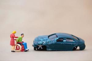 miniatuur gehandicapte man zittend in een rolstoel op een houten achtergrond, auto-ongeluk concept