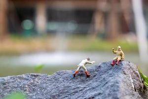 miniatuurwandelaars klimmen op een rots-, sport- en vrijetijdsconcept foto