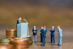 miniatuurzakenman die op een podium op een stapel muntstukken, bedrijfs en financieel investeringsconcept spreekt