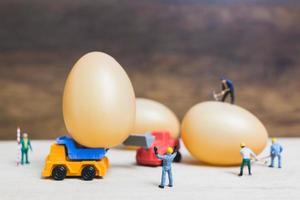 miniatuurmensen die aan paaseieren voor Pasen werken