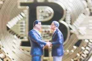 miniatuurzakenlieden die zich voor een bitcoin cryptocurrency-muntstuk bevinden, bedrijfsconcept
