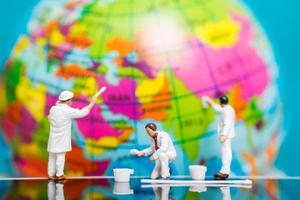 miniatuurschilders die op een bol, het concept van de aardedag schilderen foto
