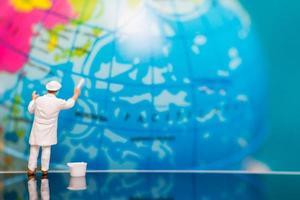 miniatuurschilder die op een bol, het concept van de aardedag schilderen foto