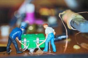 miniatuurarbeiders die samenwerken om elektronische schakelingen, bouwvakkersconcept te repareren