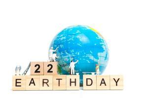 miniatuurschilders die op een wereldbol met houten blokken schilderen die dag 22 van de aarde op een witte achtergrond, het concept van de dag van de aarde tonen foto