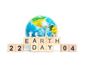 miniatuurschilders die op een wereldbol met houten blokken schilderen die dag van de aarde 22 04 op een witte achtergrond, het concept van de dag van de aarde tonen foto