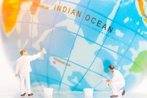 miniatuurschilders die op een wereldbol op een witte achtergrond, het concept van de dag van de aarde schilderen foto
