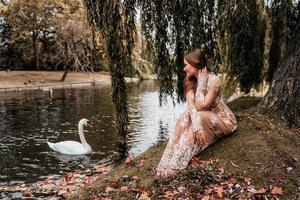 vrouw die een jurk draagt die naar een zwaan kijkt foto