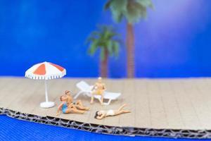 miniatuurmensen die zwemkleding dragen die op een strand met een blauwe achtergrond ontspannen foto