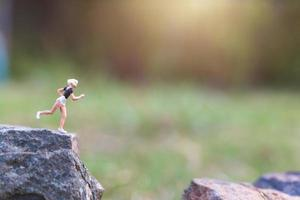 miniatuurmensen die op een rotsklif met aardachtergrond, gezondheids- en levensstijlconcept lopen foto