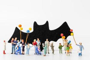 miniatuurmensen die ballons houden die op een witte achtergrond, halloween-concept worden geïsoleerd foto