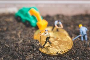 miniatuurarbeiders die de grond graven om glanzende bitcoin cryptocurrency, succesvol werkconcept te ontdekken foto